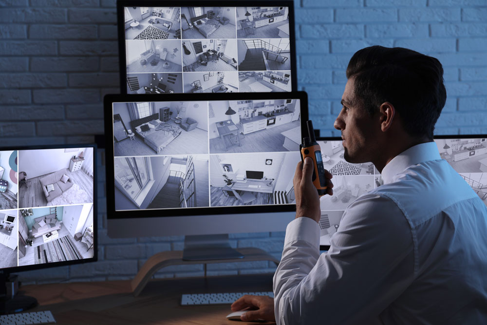 Man sitting in front of computer monitors holding a walkie talkie reviewing security cameras